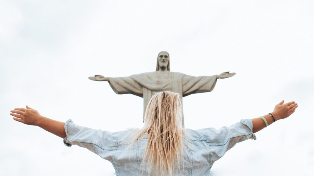 Women standing before a statue of Jesus with outstretched arms